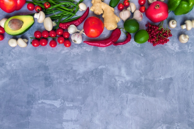 Вкусные свежие летние сырые органические антиоксидант красочные фрукты и овощи овощи: авокадо, помидоры, чеснок, перец чили, имбирь, изолированные на сером фоне. веганские и вегетарианские концепции здорового питания