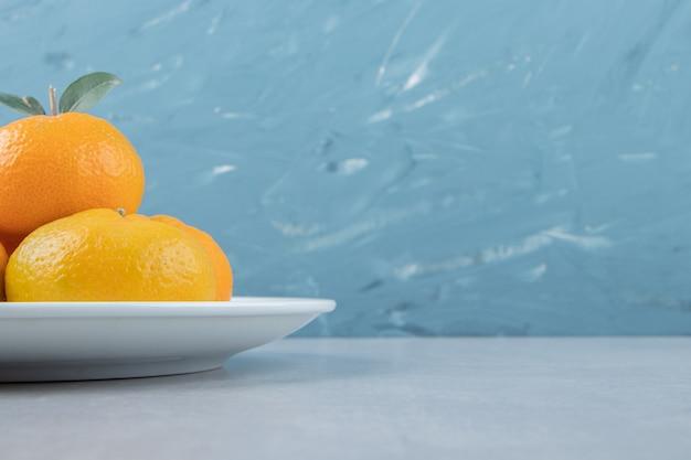 하얀 접시에 맛있는 신선한 귤.
