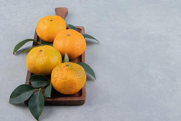 Вкусные свежие мандарины на деревянной доске.