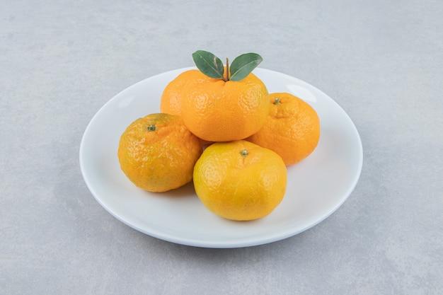 Mandarini freschi saporiti sul piatto bianco