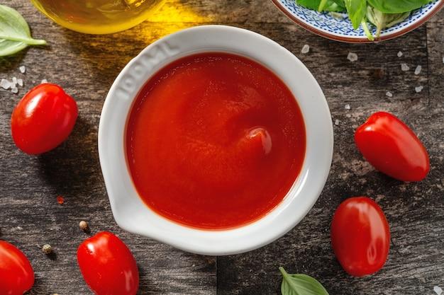 Вкусный свежий томатный соус в небольшой миске с ингредиентами для приготовления на старом деревянном столе. крупным планом