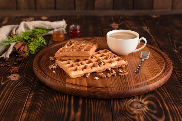 Tasty fresh vienna wafers, jam and cup of coffee on a dark wooden background