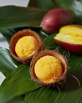 Tasty fresh yellow fruity ice cream in coconut peel with half fresh mango on green palm leaves. summer concept