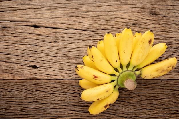 テキスト、上面図のコピースペースと素朴な天然木のテクスチャ背景においしい新鮮な黄色の熟したバナナ