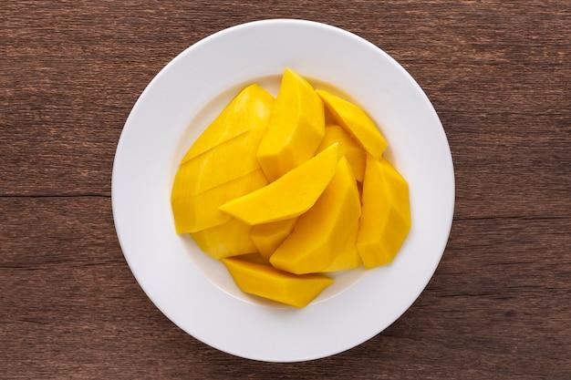 素朴な天然木の質感の背景に白いセラミックプレートでおいしい新鮮な黄色の熟したマンゴー