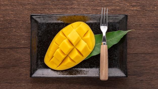 黒い長方形のセラミックプレートにフォークとマンゴーの葉が付いたおいしい新鮮な黄色の熟したマンゴー
