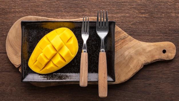 黒の長方形のセラミックプレートのオンカッティングボード、上面図のフォークでおいしい新鮮な黄色の熟したマンゴー