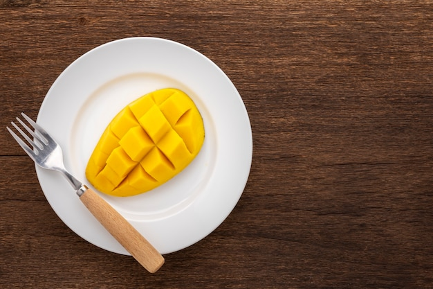 コピースペース、上面図のシンプルな白いセラミックプレートにフォークでおいしい新鮮な黄色の熟したマンゴー