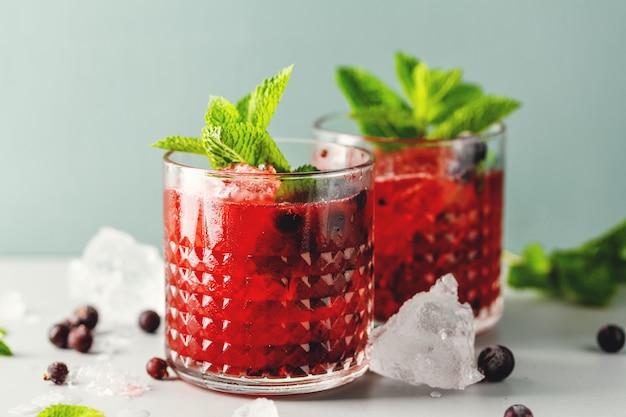 Вкусный коктейль из свежего напитка с ежевикой и мятой. подается в бокалах. крупный план