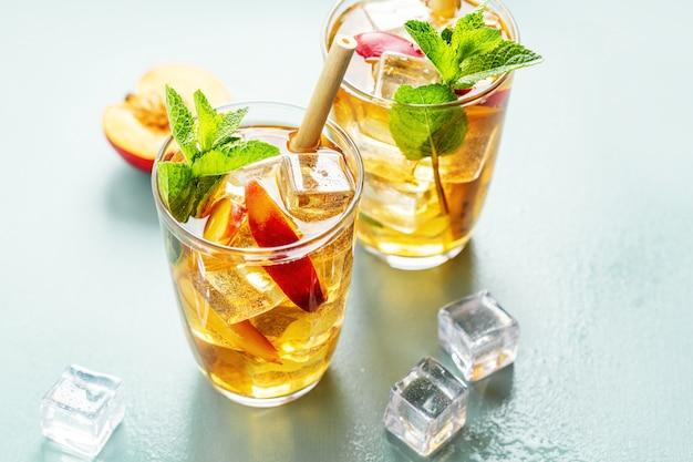 Tasty freshmade iced tea with peach, mint and ice cubes. served in glasses with bamboo straw.