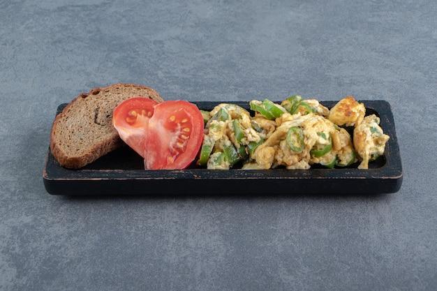 Вкусный кусок жареного яйца и ржаного хлеба на черной тарелке.