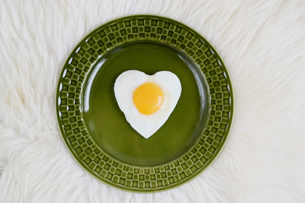 Tasty fried egg in the shape of a heart served on a green plate