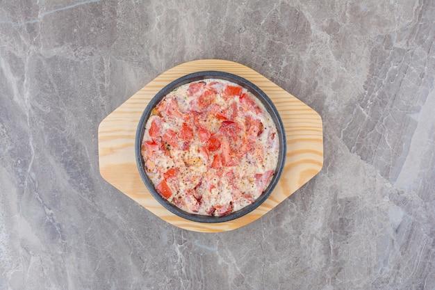 Gustose uova fritte con pomodoro in padella scura. foto di alta qualità