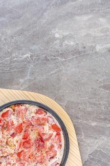 Вкусная яичница с помидорами на темной сковороде. фото высокого качества
