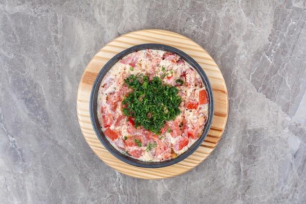 Вкусная яичница с помидорами на темной сковороде с зеленью. фото высокого качества