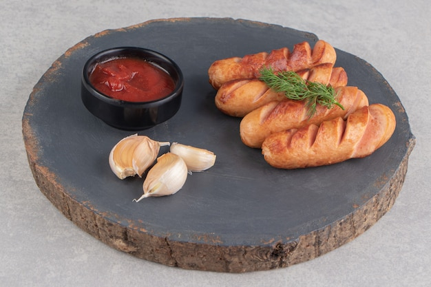 Tasty fried sausages, garlic and ketchup on wood piece.