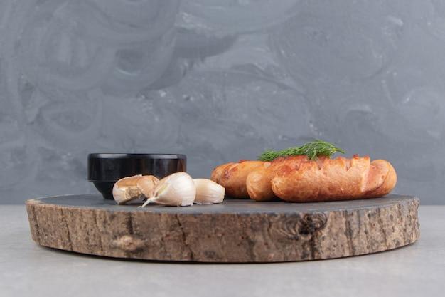 Gustose salsicce fritte, aglio e ketchup su un pezzo di legno.