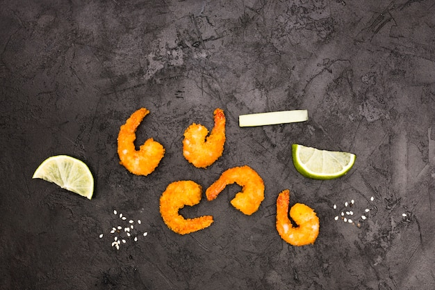 Tasty fried shrimps and juicy lemon wedges over textured concrete wall