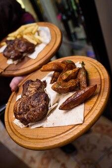 Вкусные жареные стейки и картофель в деревенском стиле на деревянных подносах