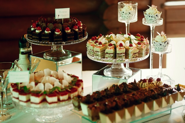 Tasty fruit and chocolate cakes stand on glass plates