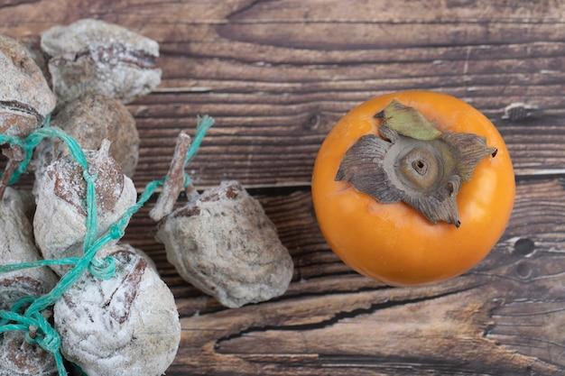 Вкусная хурма фую и сушеная хурма на деревянной поверхности