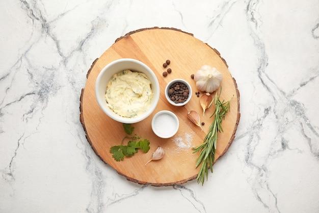 Вкусное чесночное масло и ингредиенты на светлом фоне