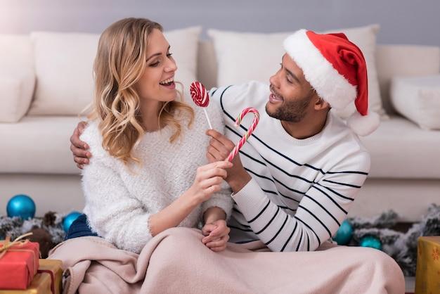 맛있는 선물. 막대 사탕을 들고 서로를 보면서 교환 긍정적 인 즐거운 행복한 커플