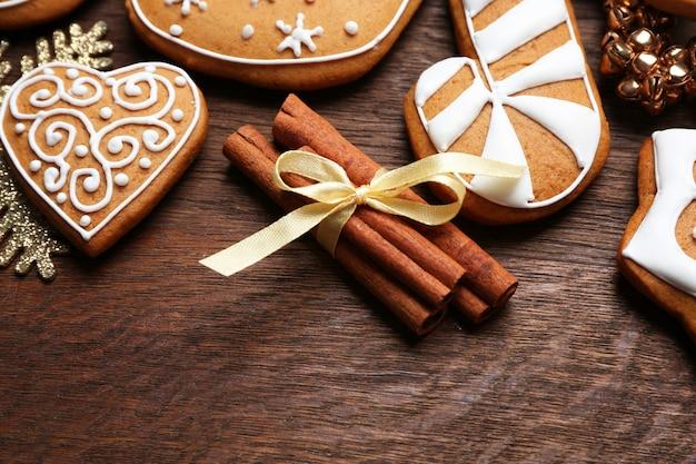 木製の背景においしいジンジャーブレッドクッキーとクリスマスの装飾、クローズアップ