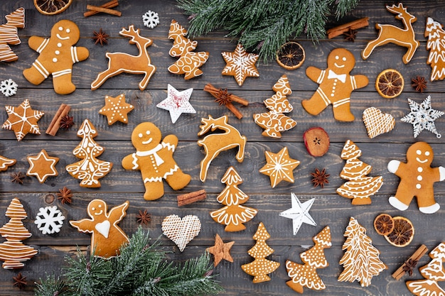 나무 배경에 맛있는 진저브레드 쿠키와 크리스마스 장식이 있습니다.