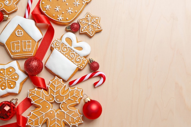 Tasty gingerbread cookies and christmas decor on wooden background