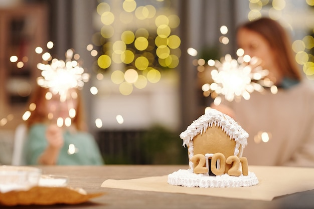 Tasty gingerbread house decorated with whipped cream standing on table