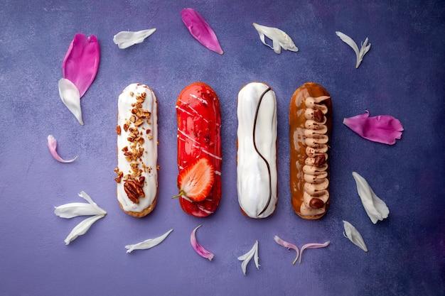 Набор вкусных глазурованных эклеров, шоколад, клубника, орехи, сливки, украшенный листьями розового цветка, горизонтальный вид сверху, вид сверху, место для текста