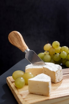 Tasty grapes with brie cheese on a board