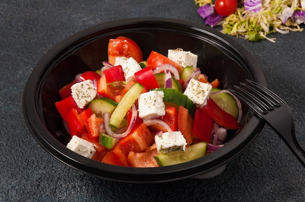 Вкусный греческий салат в черной пластиковой миске concept food delivery