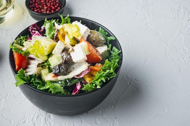 Вкусный греческий салат с фетой, оливками и помидорами на белом фоне с местом для текста