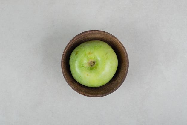 木製のボウルにおいしい青リンゴ