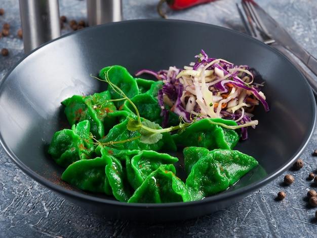 濃い色の皿に魚と野菜が入ったおいしい緑の餃子