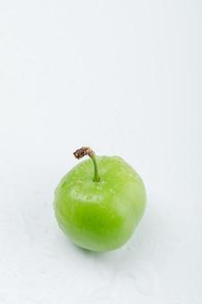 Вкусная зеленая слива высокий угол зрения на белой стене