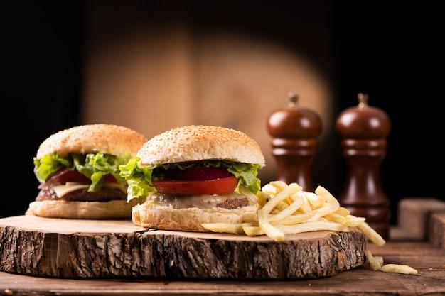 Вкусный гамбургер из говядины на гриле с салатом, сыром и луком, подается на разделочной доске с copyspace