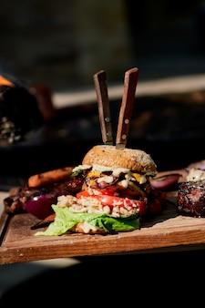 Вкусный гамбургер на гриле с говядиной, чизбаконом и соусом на деревянном столе с картофелем фри и пивом