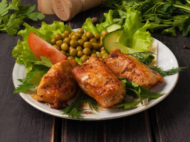 Вкусная куриная грудка гриль, украшенная овощами на белой тарелке