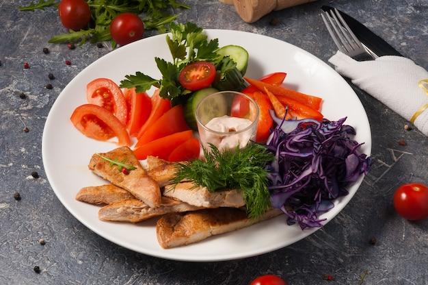 Вкусная куриная грудка на гриле со свежими овощами. горизонтальная рамка