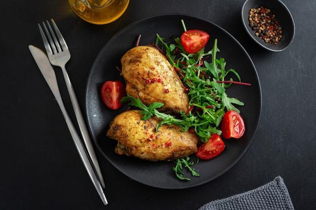 Вкусная куриная грудка на гриле с овощами и салатом на темном столе.