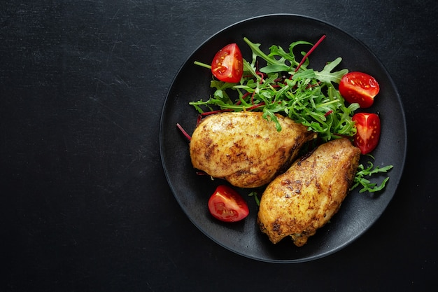 Tasty grilled chicken breast with vegetables and salad served on dark table
