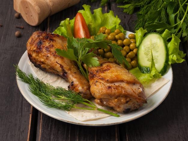 하얀 접시에 야채로 장식 된 맛있는 구운 치킨 드럼 스틱