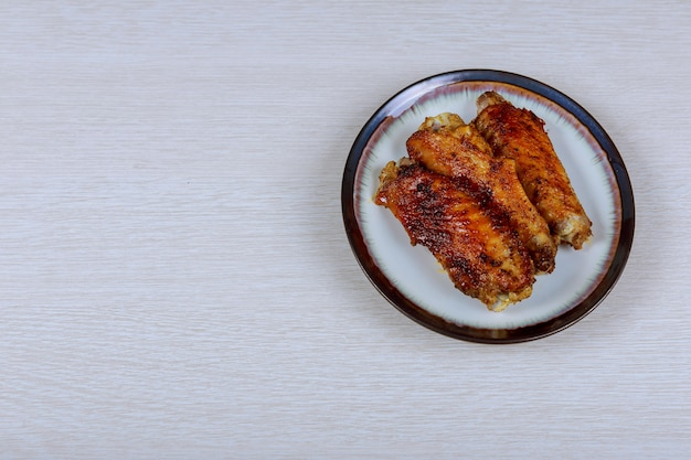 Tasty grilled chicken wings on a white dish, top view