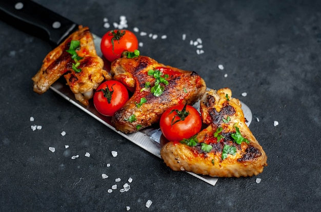 Tasty grilled chicken wings with spices and herbs