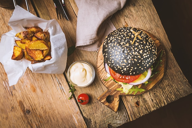 Tasty grilled classic beef black burger with lettuce and mayonnaise sauce on a rustic wooden table top view with copy space