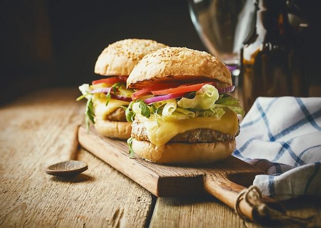 素朴な木製のテーブルにレタスとマヨネーズソースを添えたおいしいグリルクラシックビーフバーガー