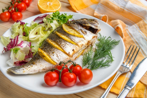레몬과 허브와 함께 맛있는 구운 dorado 물고기는 토마토와 샐러드와 함께 접시에 제공됩니다. 보기를 닫습니다.